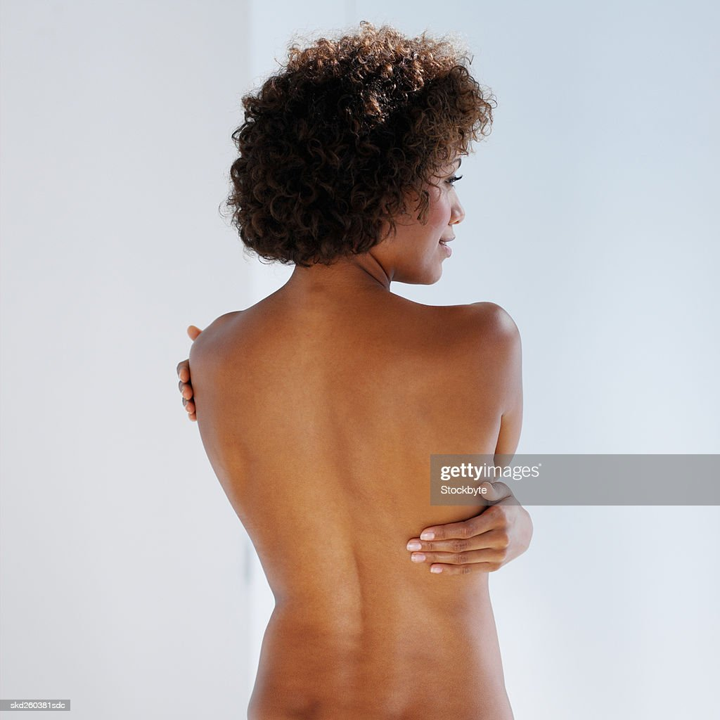 Rear view of a nude woman standing : Stock Photo