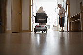 Rear view of a disabled nun sitting in a motorized wheelchair in a church