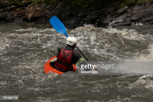 Rear view of a person kayaking in a river : Stock Photo