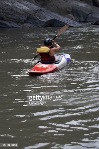 Rear view of a person kayaking in a river : Foto de stock