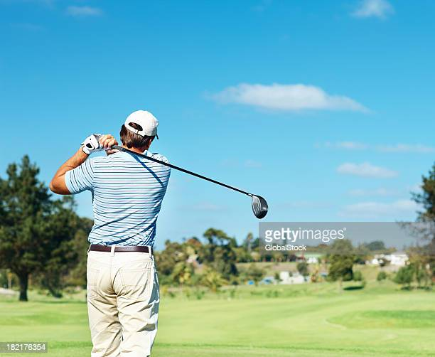 Rear view of a professional golfer practicing