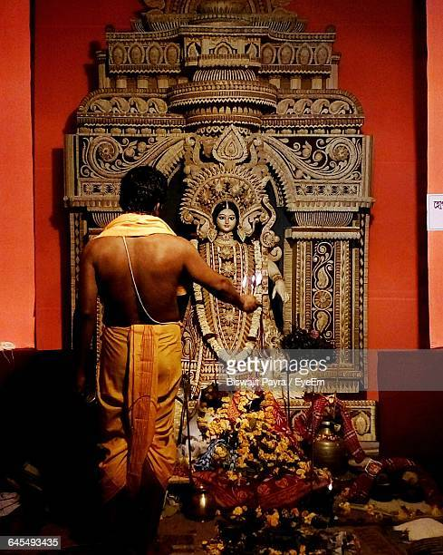Rear View Of A Religious Man Praying At Hindu Goddess