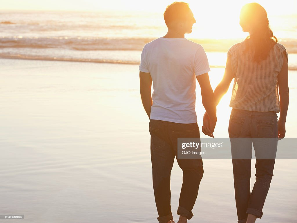 Rear view of a romantic couple walking at beach holding hands : Stock Photo