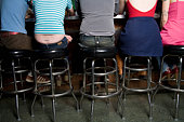Rear view of a row of friends sitting at a bar counter
