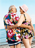 Rear View of a Senior Couple in Colourful Swimwear Standing on the Beach With Their Arms Around Each Other