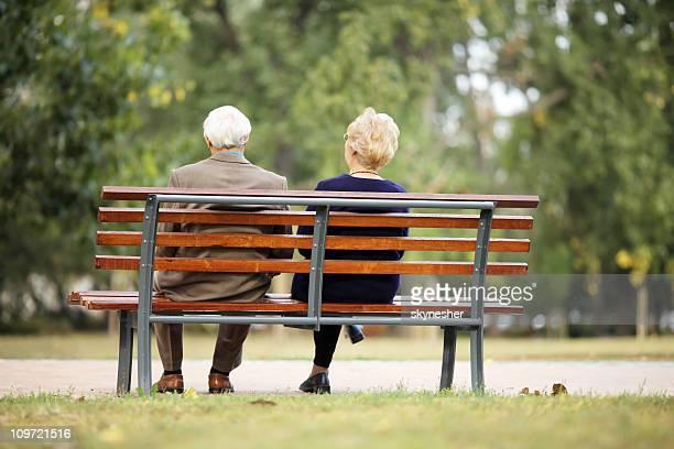 Rückansicht des altes Paar sitzen auf der Bank im Freien.