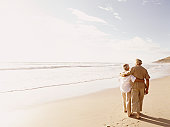 Rear View of a Senior Couple Walking on a Beach With Their Arms Around Each Other