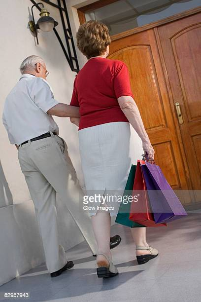 Rear view of a senior couple walking with shopping bags