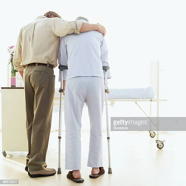 rear view of a son helping his father walk with crutches