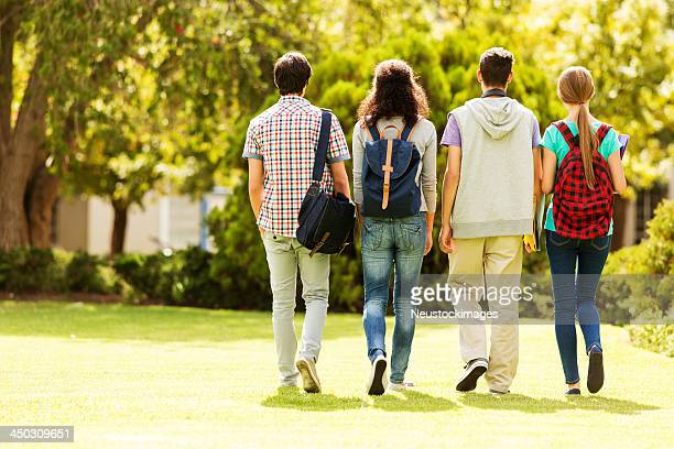 Rear View Of A Student Group Walking On Campus