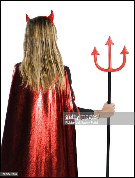 Rear view of a teenage girl wearing a devil costume holding a pitchfork