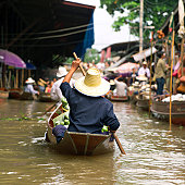 Rear view of a vendor rowing a boat at a floating market, Bangkok, Thailand