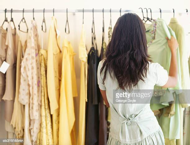 rear view of a woman choosing a dress in a clothing store