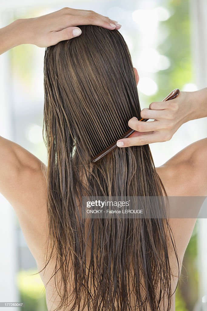 Rear view of a woman combing her hair : Stock Photo