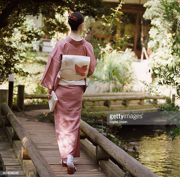 Rear View of a Woman Holding a Book and Walking on a Wooden Bridge