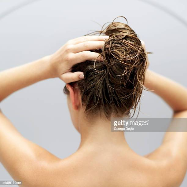 rear view of a woman holding her hair up