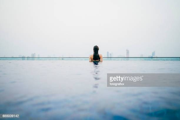 rear view of a woman in infinity pool, cityscape