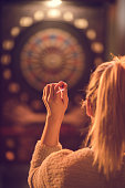 Back view of woman aiming at dartboard in a pub. Focus is on her hand.