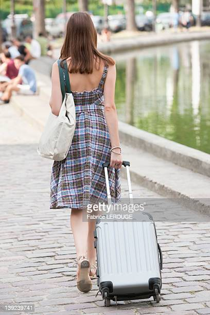 Rear view of a woman pulling a suitcase, Paris, Ile-de-France, France