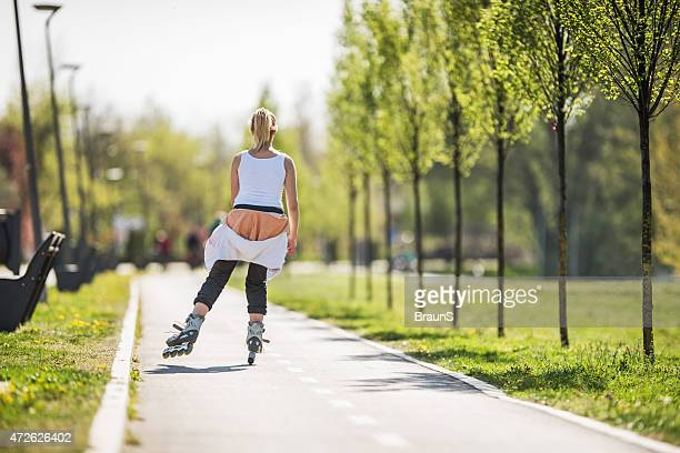 Rear view of a woman roller skating in the park.