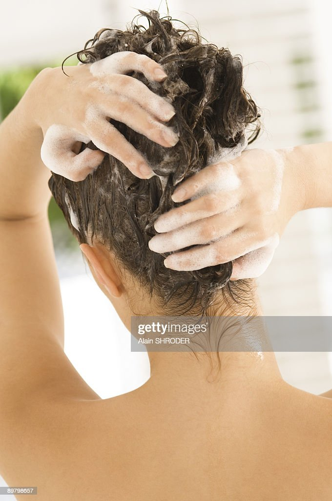 Rear view of a woman shampooing her hair