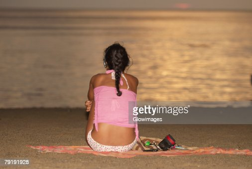 Rear view of a woman sitting on the beach, Taganga Bay, Departamento De Magdalena, Colombia : Foto de stock