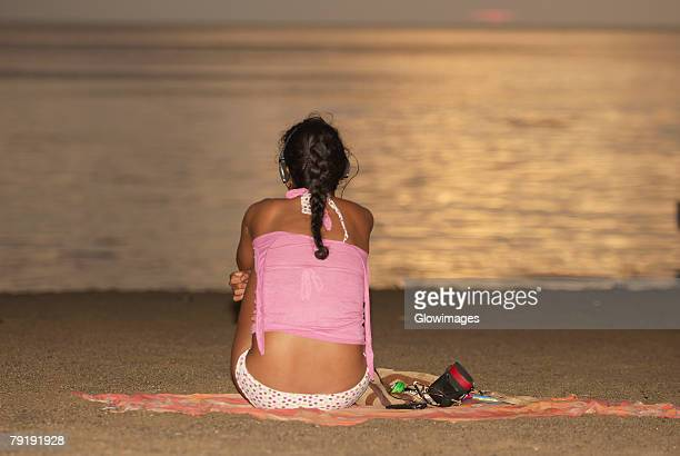 Rear view of a woman sitting on the beach, Taganga Bay, Departamento De Magdalena, Colombia