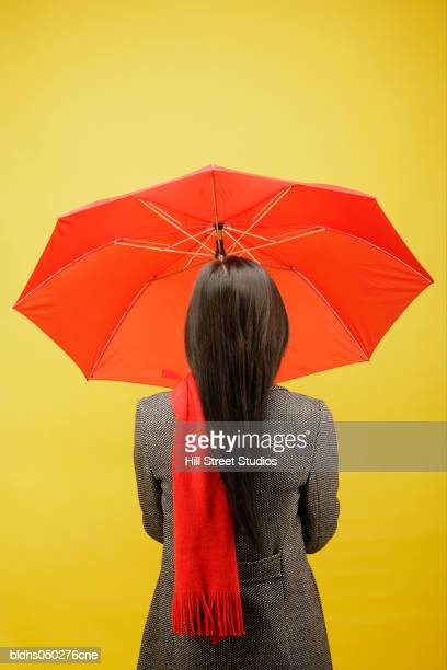 Rear view of a woman standing holding an umbrella