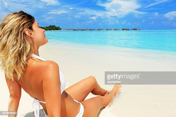 Vista posteriore di una donna prendere il sole sulla spiaggia tropicale.