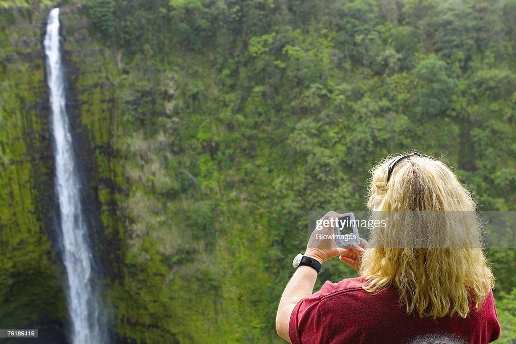 Rear view of a woman taking a photograph of a waterfall, Akaka Falls, Akaka Falls State Park, Hilo, Big Island, Hawaii Islands, USA : Foto de stock