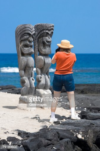Rear view of a woman taking a photograph of tikies on the coast, Puuhonua O Honaunau National Historical Park, Kona Coast, Big Island, Hawaii Islands, USA : Stock Photo