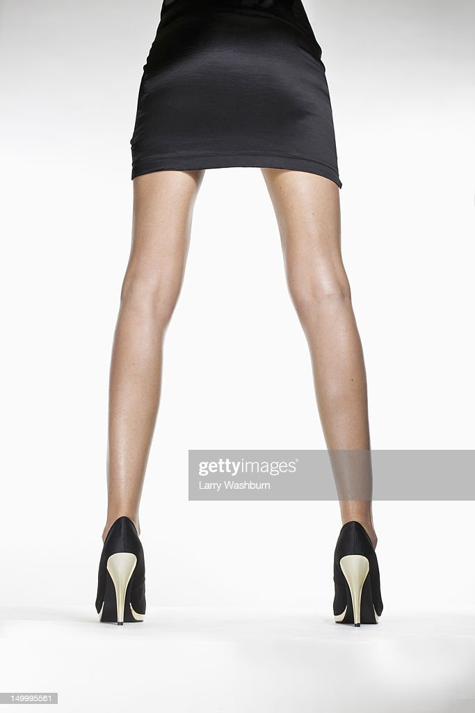 Rear view of a woman wearing a skirt and high heels, waist down