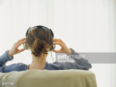 Rear view of a woman wearing headphones : Stock Photo