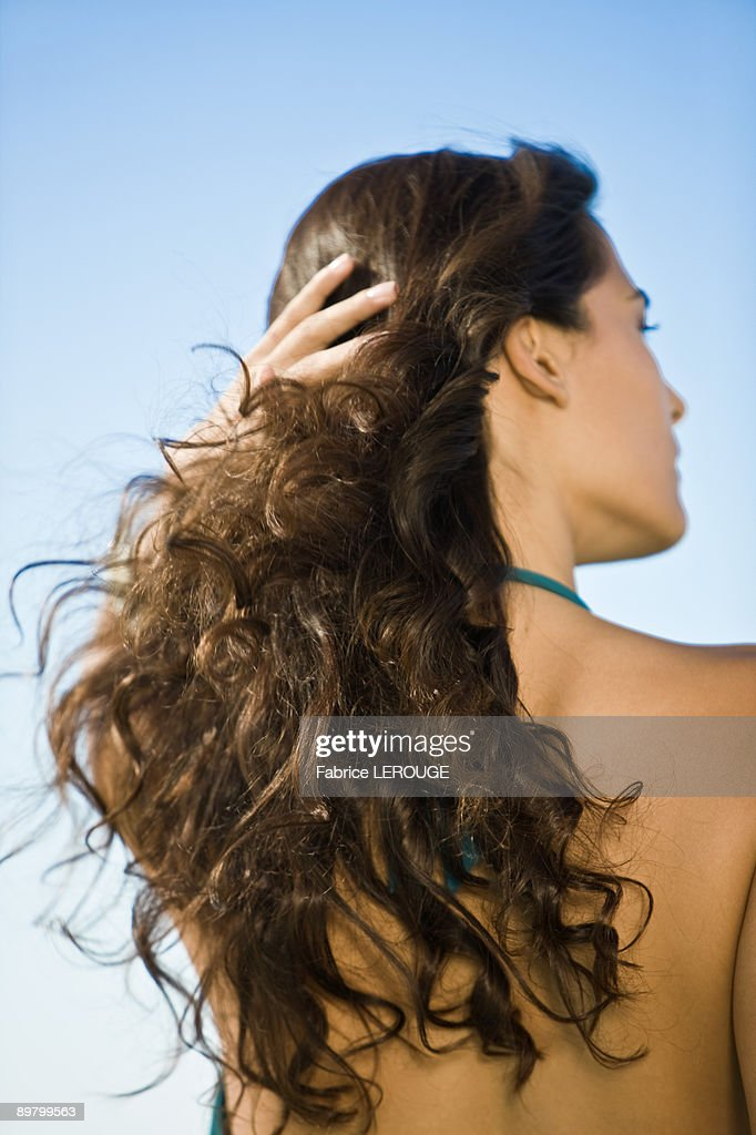 Rear view of a woman with her hand in her hair