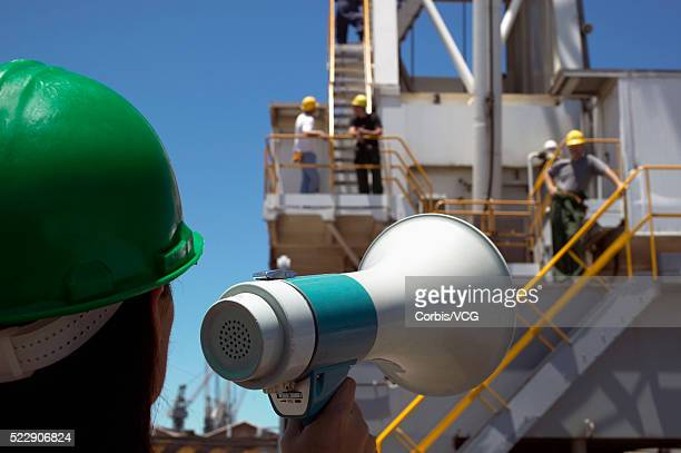 Rear view of a worker in a hard hats using a megaphone to talk to workers on a high platform