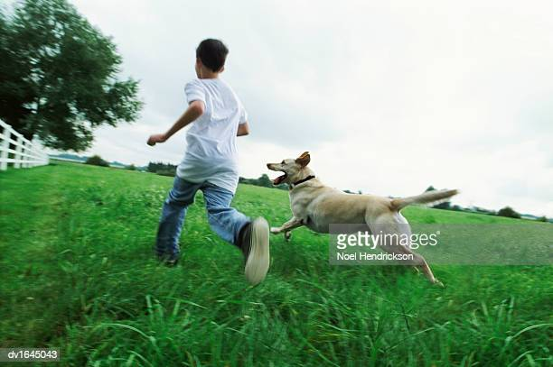 Rear View of a Young Boy Running Side by Side With His Pet Dog in a Country Field