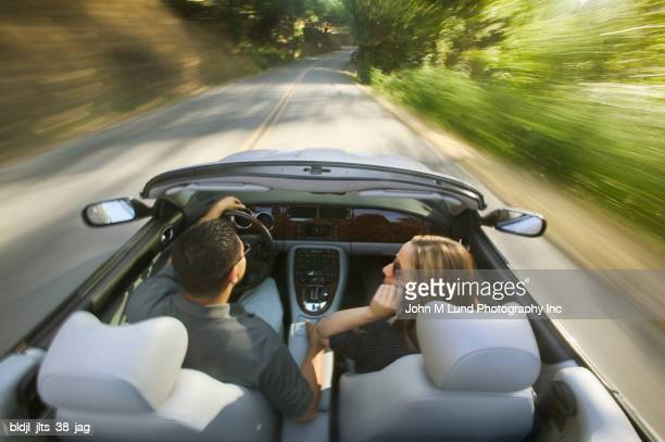 Rear view of a young couple driving in a convertible car