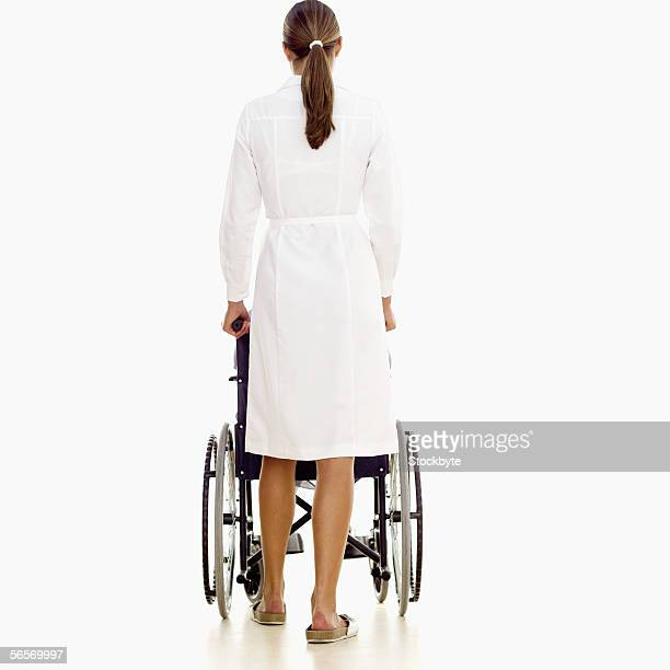 rear view of a young female nurse pushing a wheelchair