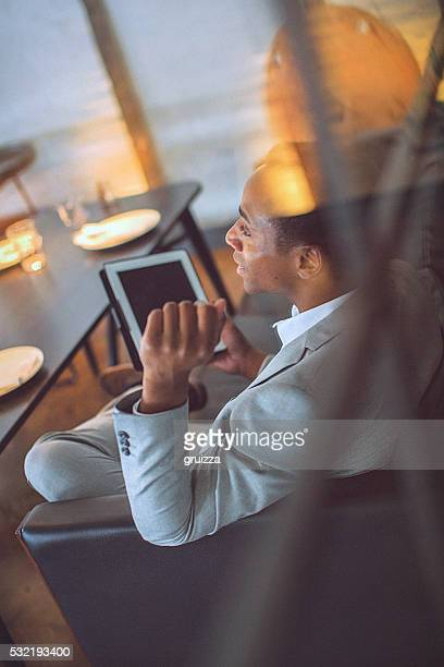 Rear view of a young handsome businessman holding tablet