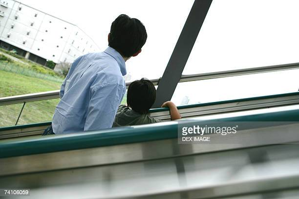 Rear view of a young man and his son on an escalator