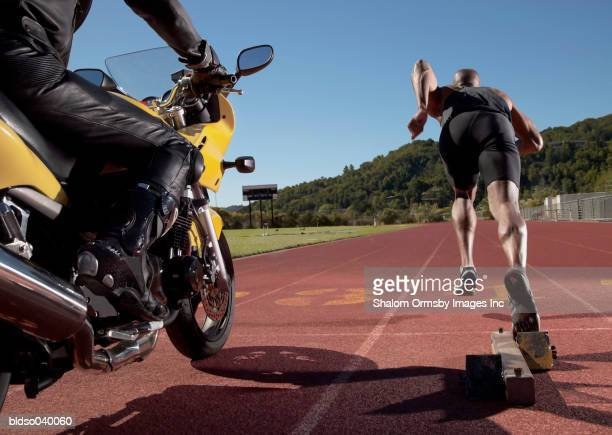 Rear view of a young man at the starting position on a running track along side a motorcycle