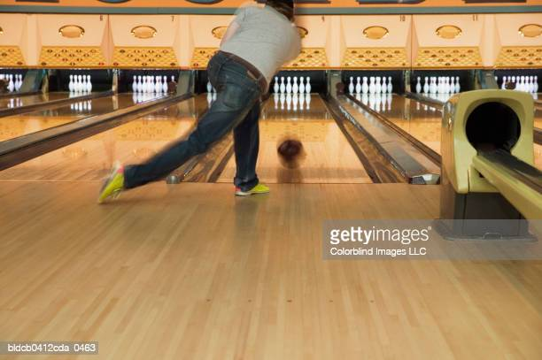 Rear view of a young man bowling