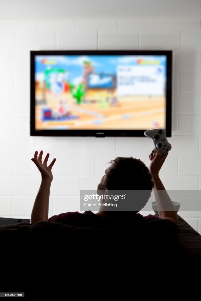 Rear view of a young man gesturing on a sofa while playing XBox 360 video games on a wall-mounted television, taken on July 9, 2013.