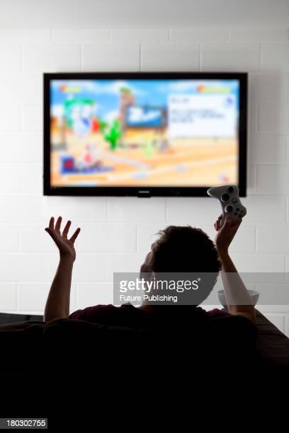 Rear view of a young man gesturing on a sofa while playing XBox 360 video games on a wallmounted television taken on July 9 2013