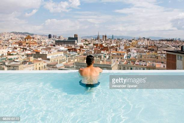 Rear view of a young man relaxing in the pool and looking at Barcelona city skyline