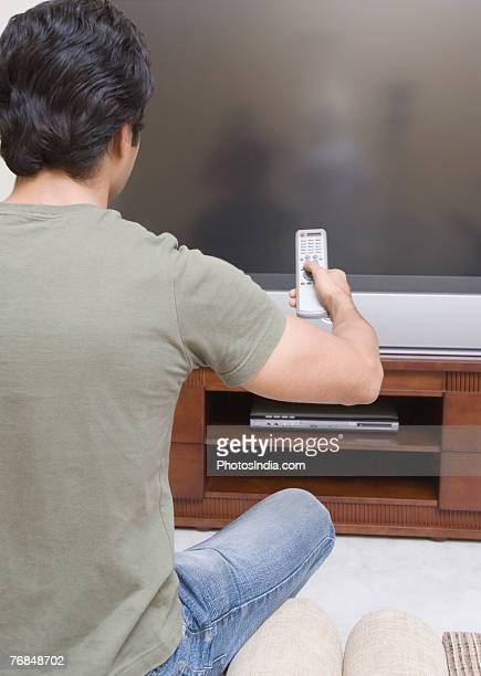 Rear view of a young man sitting on a couch and operating a remote control