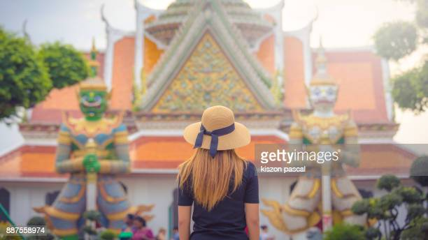 Rear view of a young tourist women visiting temple in Thailand . . Asia