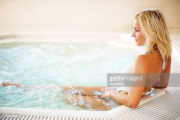 Rear view of a young woman enjoying in the Jacuzzi.