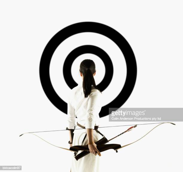 Rear view of a young woman holding a crossbow looking at a target