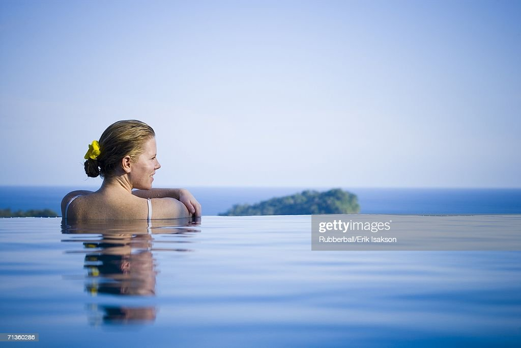 Rear view of a young woman in a swimming pool : Stock Photo